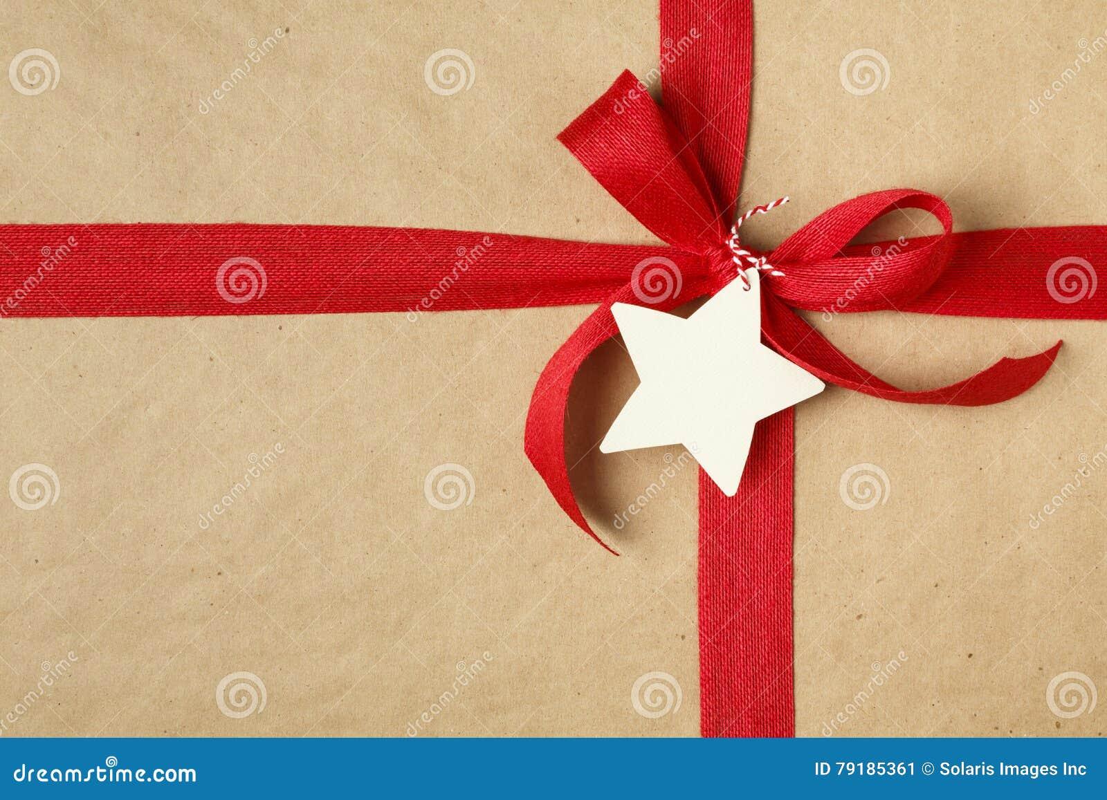 Bożenarodzeniowy prezent z łęku i pustego miejsca prezenta etykietką Prosty przetwarzający opakunkowego papieru tło i naturalny j