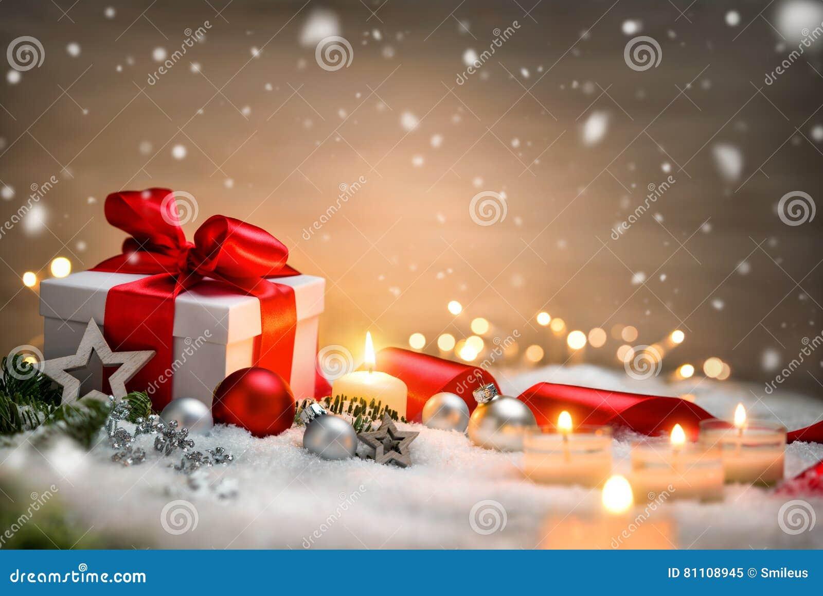 Bożenarodzeniowy prezent z śniegiem, świeczkami i ornamentami,