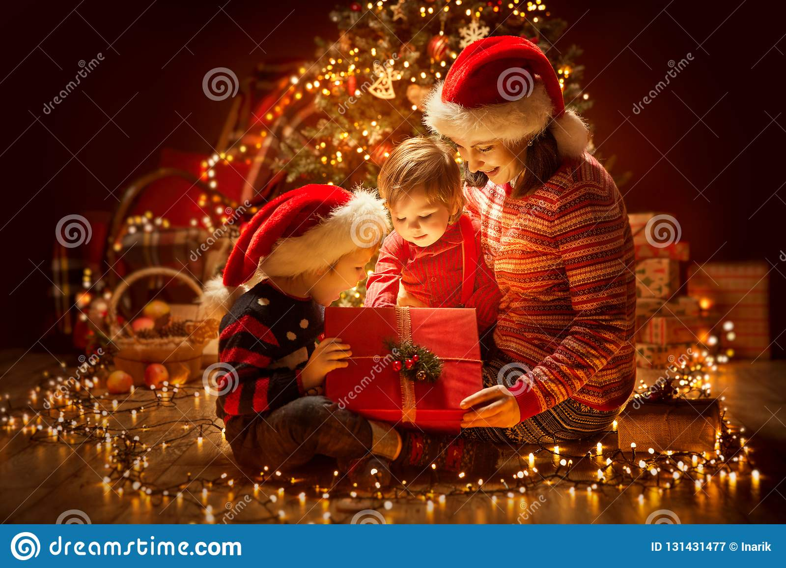 Bożenarodzeniowy Rodzinny otwarcia oświetlenia teraźniejszości prezenta pudełko pod Xmas drzewem, Szczęśliwą matką i dziećmi,