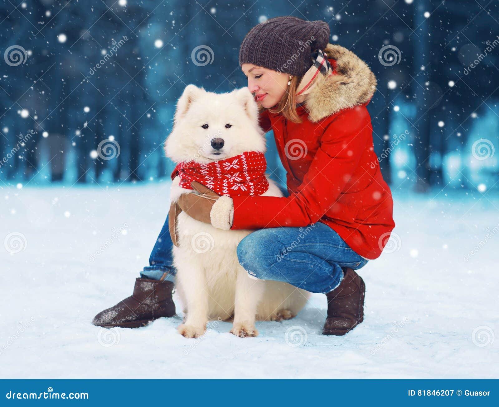 Bożenarodzeniowy szczęśliwy młoda kobieta właściciel migdali obejmujący białego Samoyed psa na śniegu w zimie nad płatkami śniegu