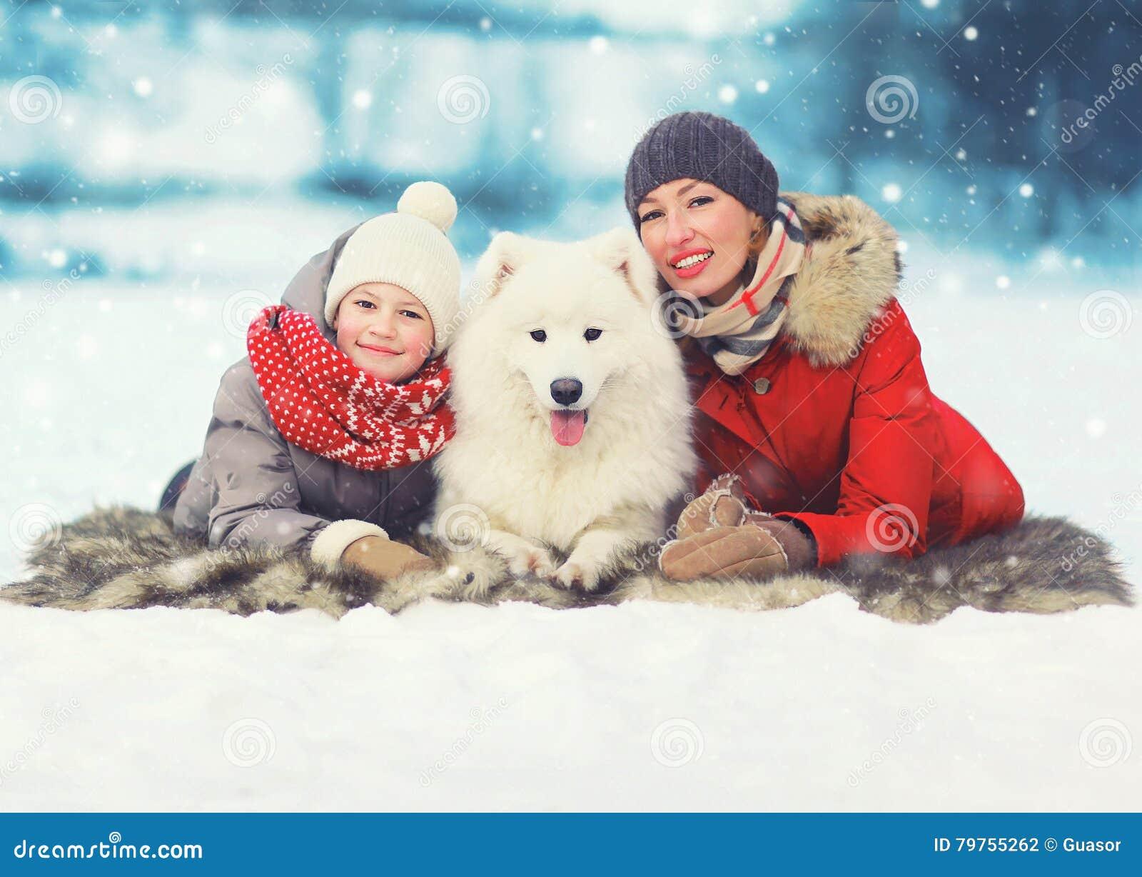 Bożenarodzeniowy szczęśliwy uśmiechnięty rodziny, matki i syna dziecka odprowadzenie z białym Samoyed psem w zima dniu, kłama na