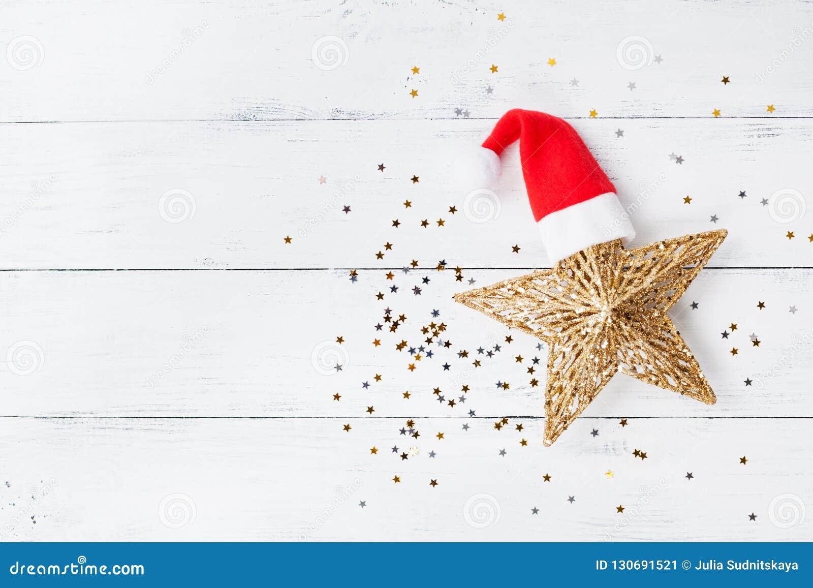 Bożenarodzeniowy tło złota gwiazda z Santa confetti i kapeluszu odgórnym widokiem Mieszkanie nieatutowy