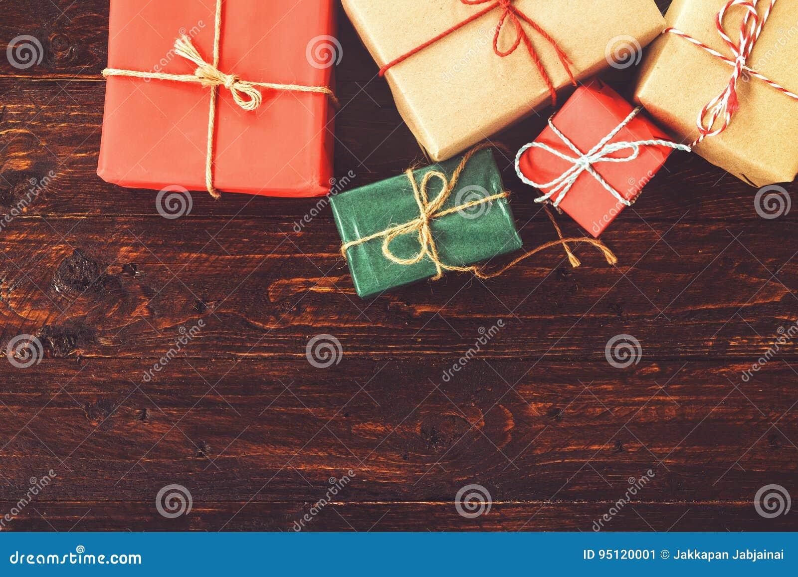 Bożenarodzeniowy tło z dekoracjami i handmade prezentów pudełkami na starej drewnianej desce