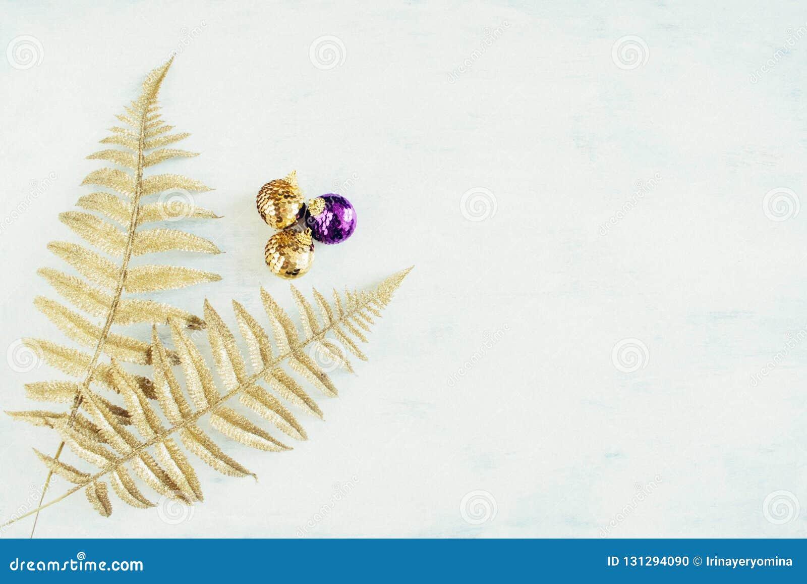 Bożenarodzeniowy wakacyjny świąteczny temat z złotymi fiołkowymi bożymi narodzeniami ornamentuje i złocista dekoracyjna paproć op