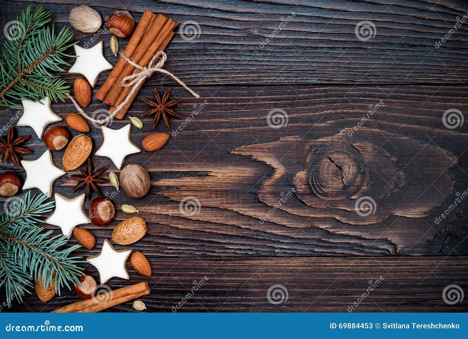 Bożenarodzeniowy wakacyjny tło z piernikowymi ciastkami i jodłą rozgałęzia się na starej drewnianej desce kosmos kopii