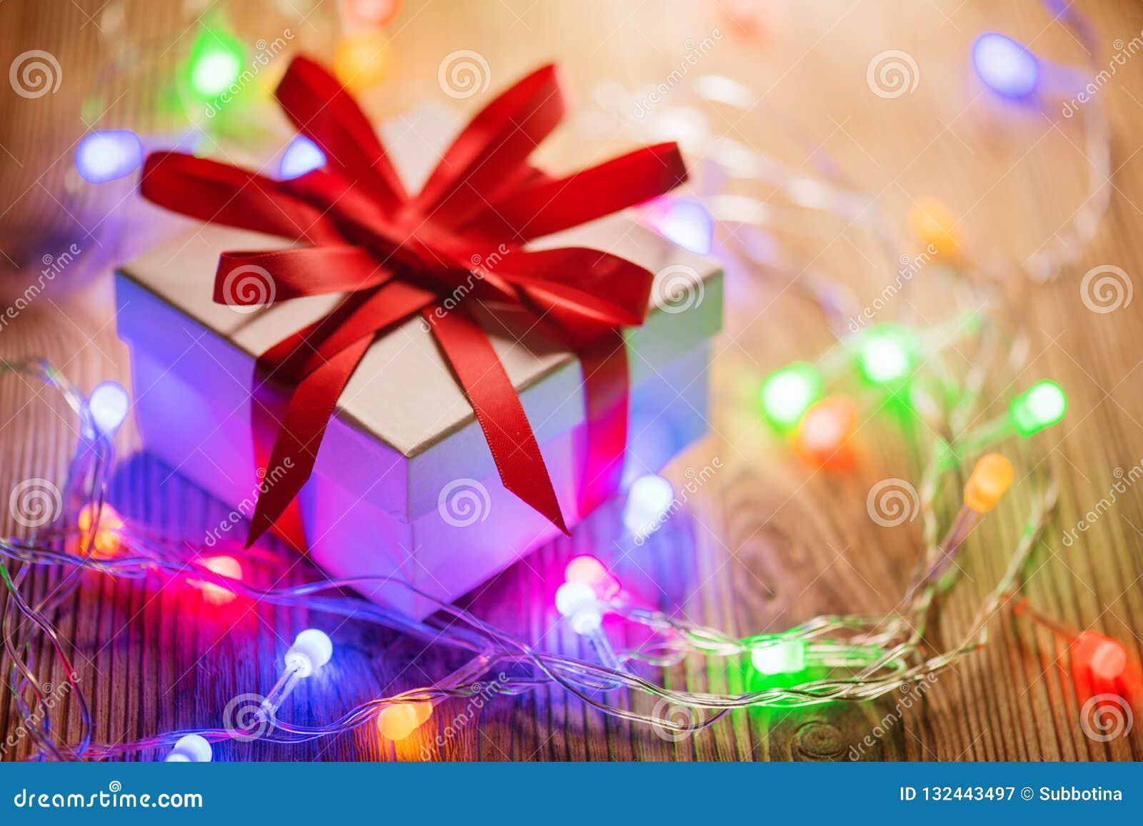 Bożenarodzeniowy Wakacyjny Tło Zawijający prezenta pudełko z czerwonym jedwabniczym faborkiem i kolorowa światło girlanda nad dre