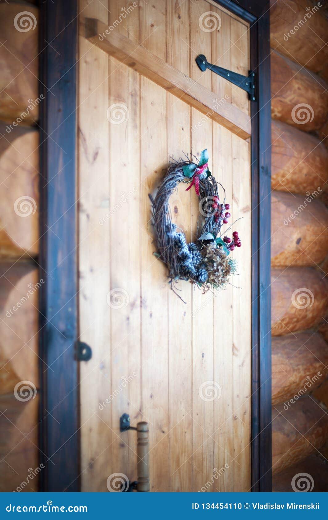 Bożenarodzeniowy wianek na drewnianym drzwi w bela domu