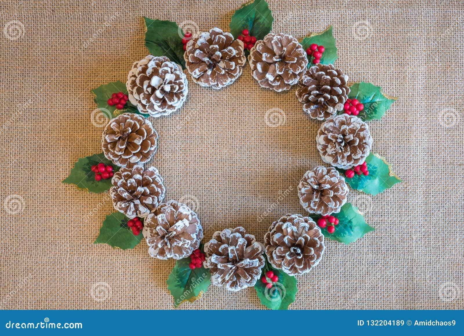 Bożenarodzeniowy wianek pinecones, uświęconi liście i czerwone jagody na nieociosanym tkaniny tle,