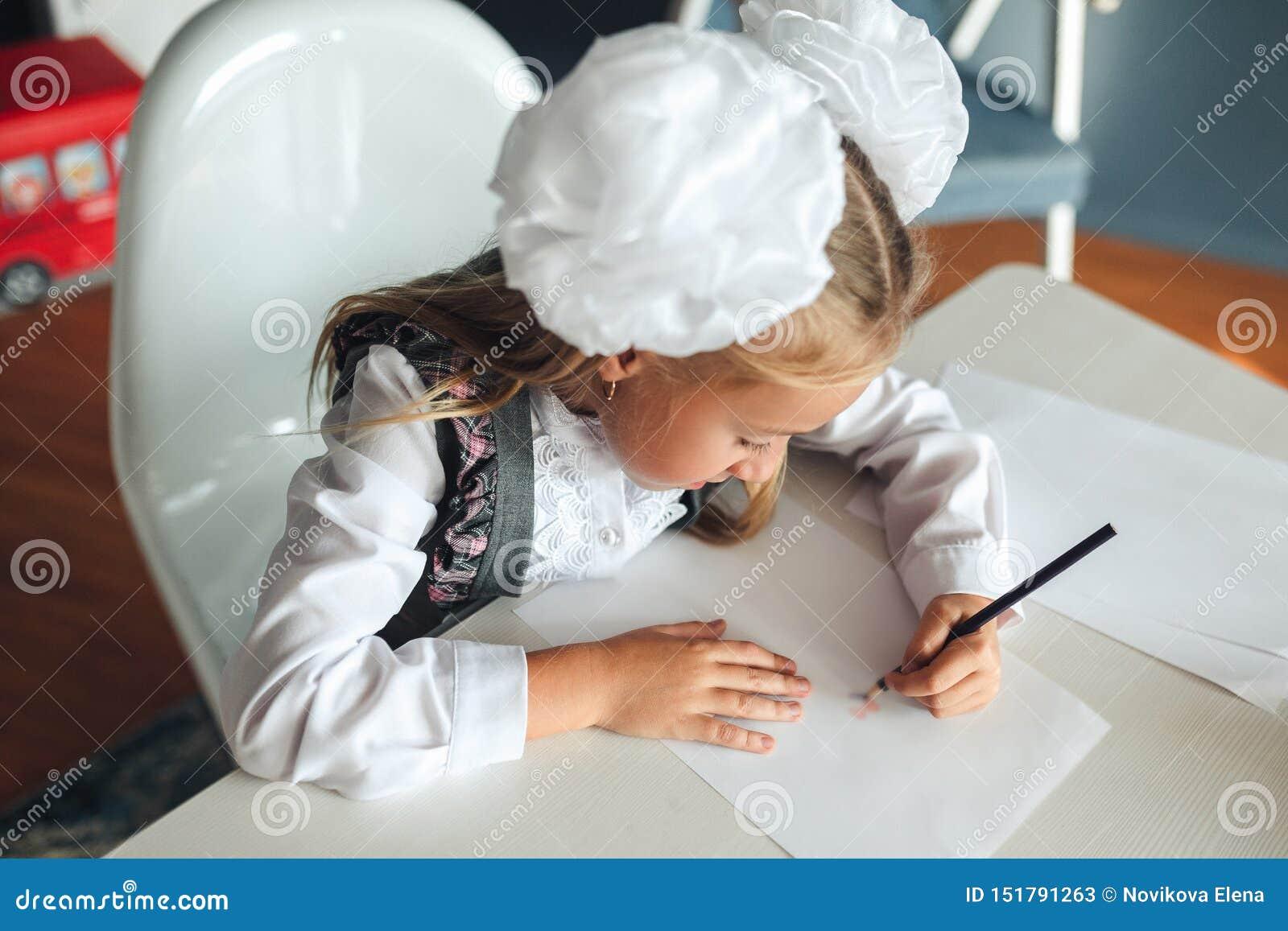 Boa imagem do desenho bonito da estudante com lápis coloridos ao sentar-se na tabela durante a lição da arte na escola estudante