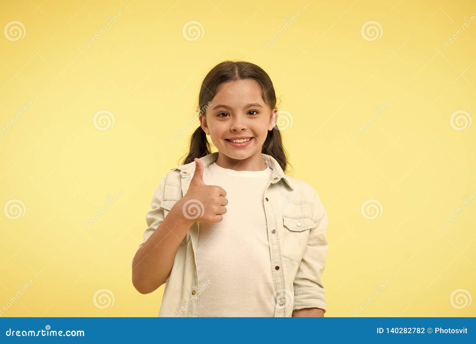 Boa qualidade O polegar das mostras da menina da criança acima do gesto recomenda o fundo amarelo A criança recomenda altamente c
