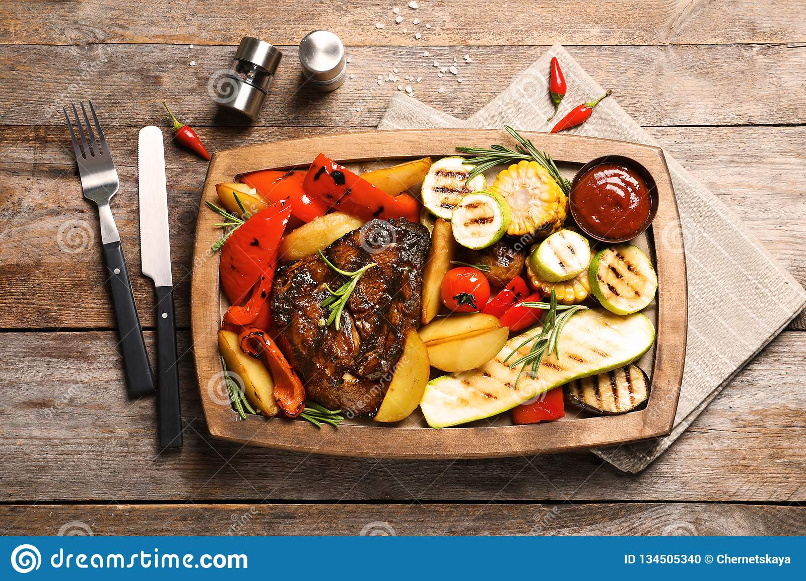 Board with barbecued steak, garnish and sauce on wooden background