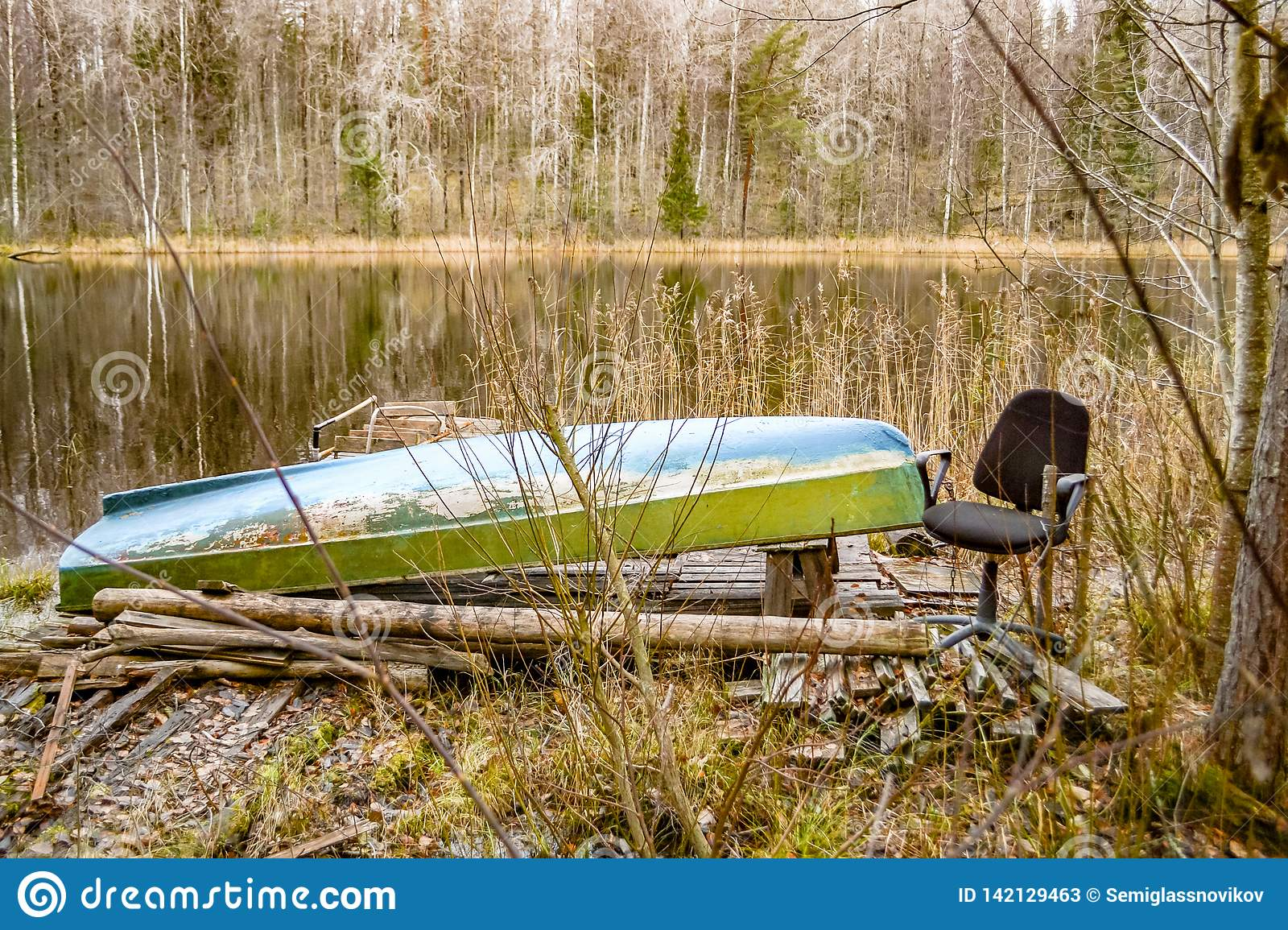 Boat and chair on the coast of wild lake