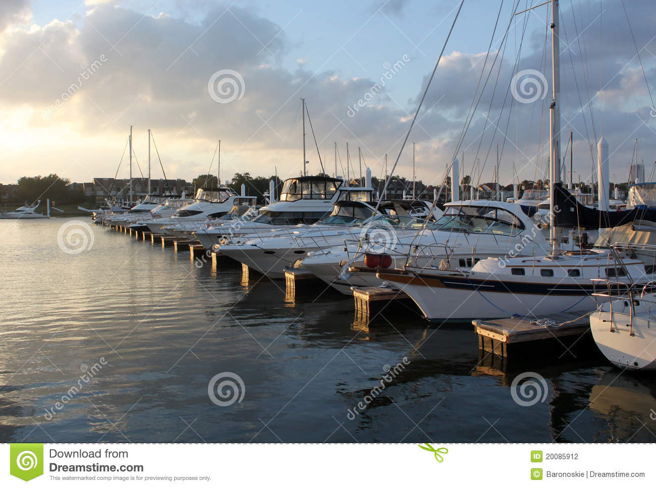 Many boats are lined up in a dock.