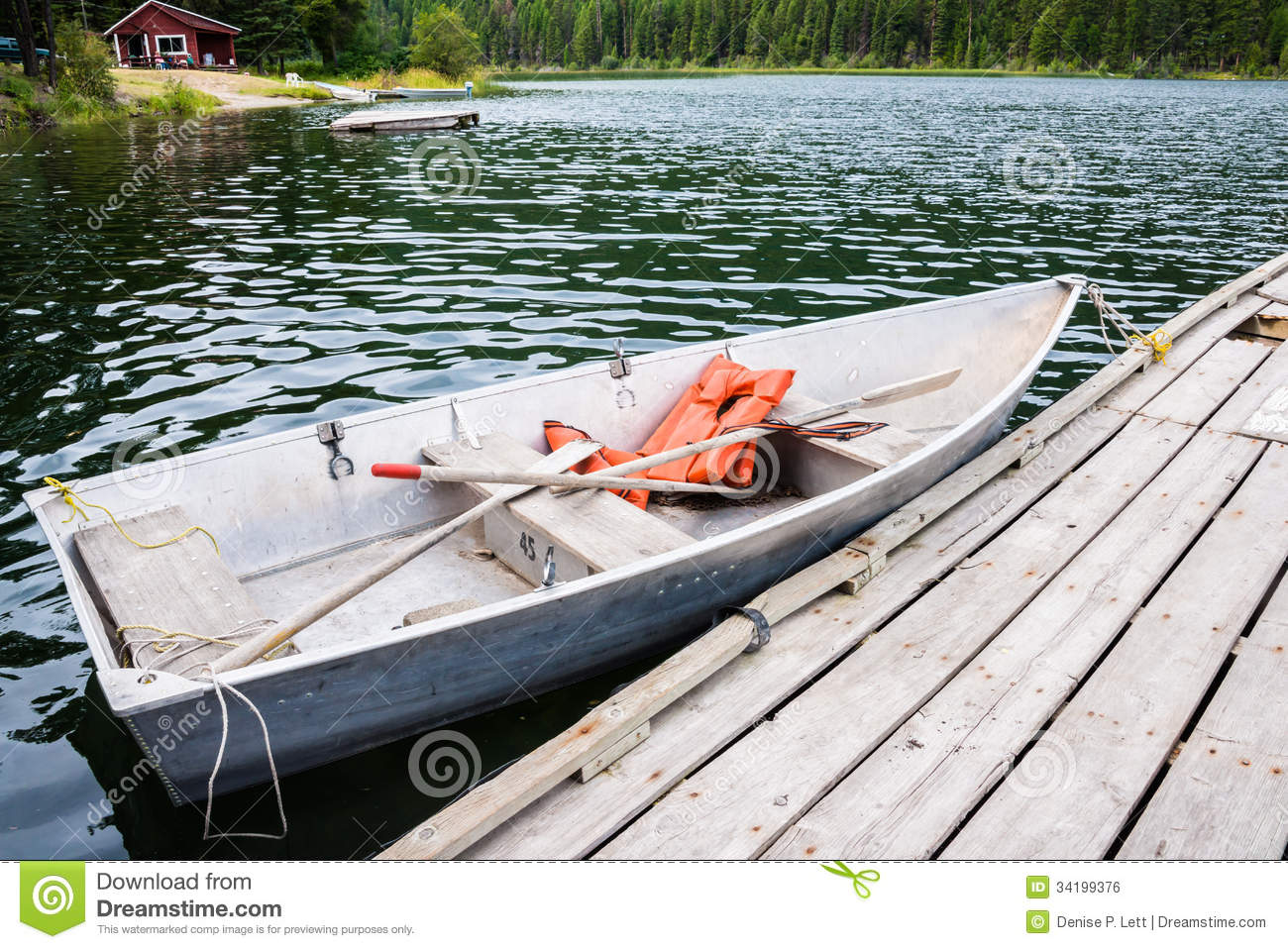 Old row boat with life jackets and oars moored to dock in lake. Copy ...