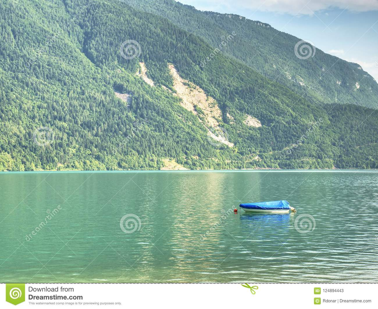 Boat On Green Blue Water Level Of Alps Lake  White Shore Of