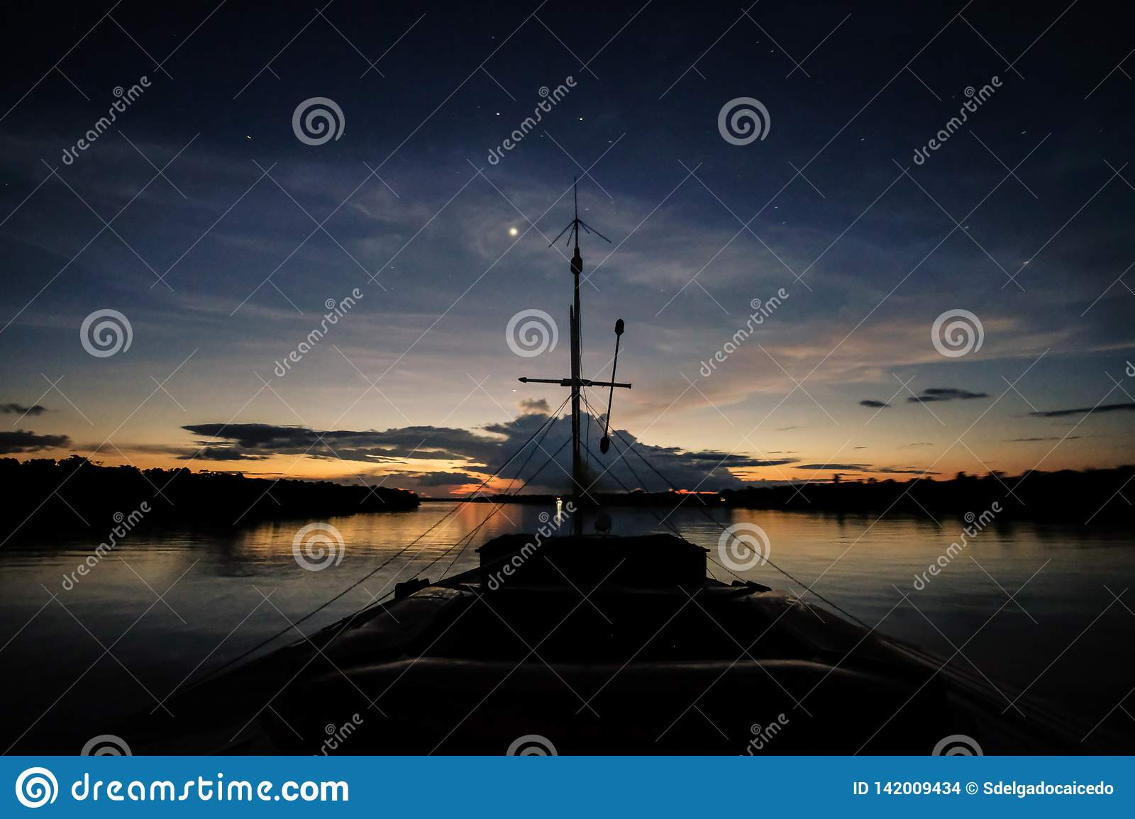 A boat navigates the Javari River after the sunset