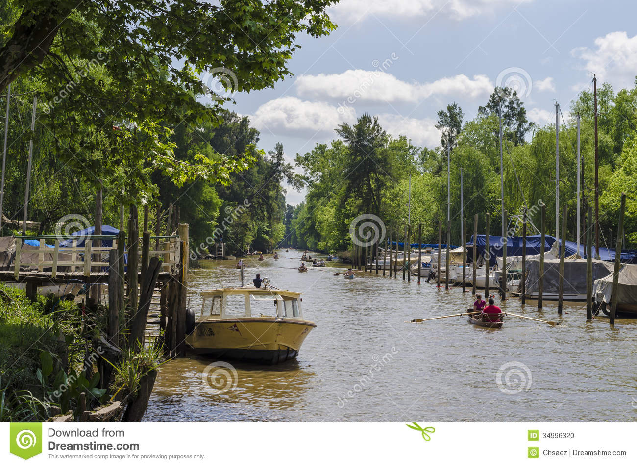 Boat in pier, and several canoes rowing along canal in Tigre, Buenos ...