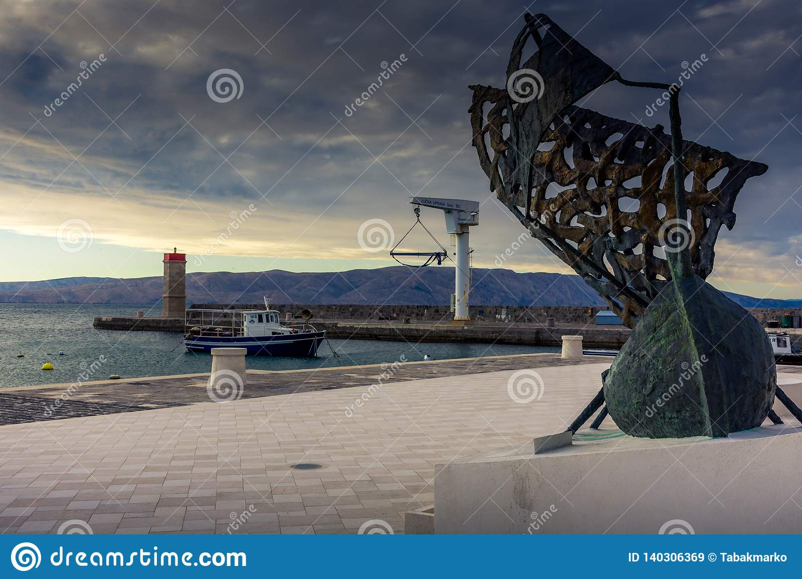 A boat in a port with a statue of a sailing boat in foreground
