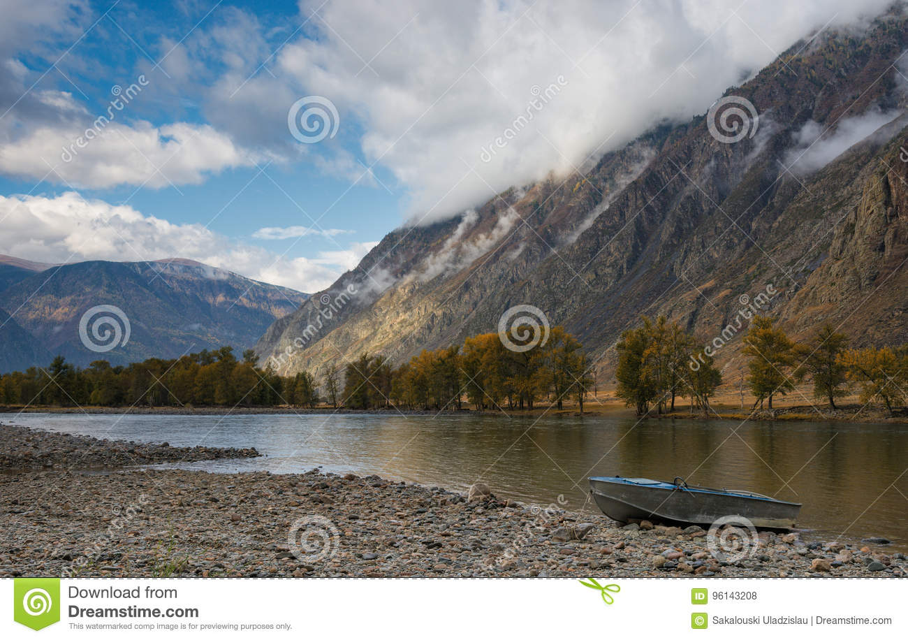 Boat On The Shore. Autumn Mountain Landscape With A River Valley, Beautiful Cloudy Sky And Aluminum Boat On A Stony Shore.
