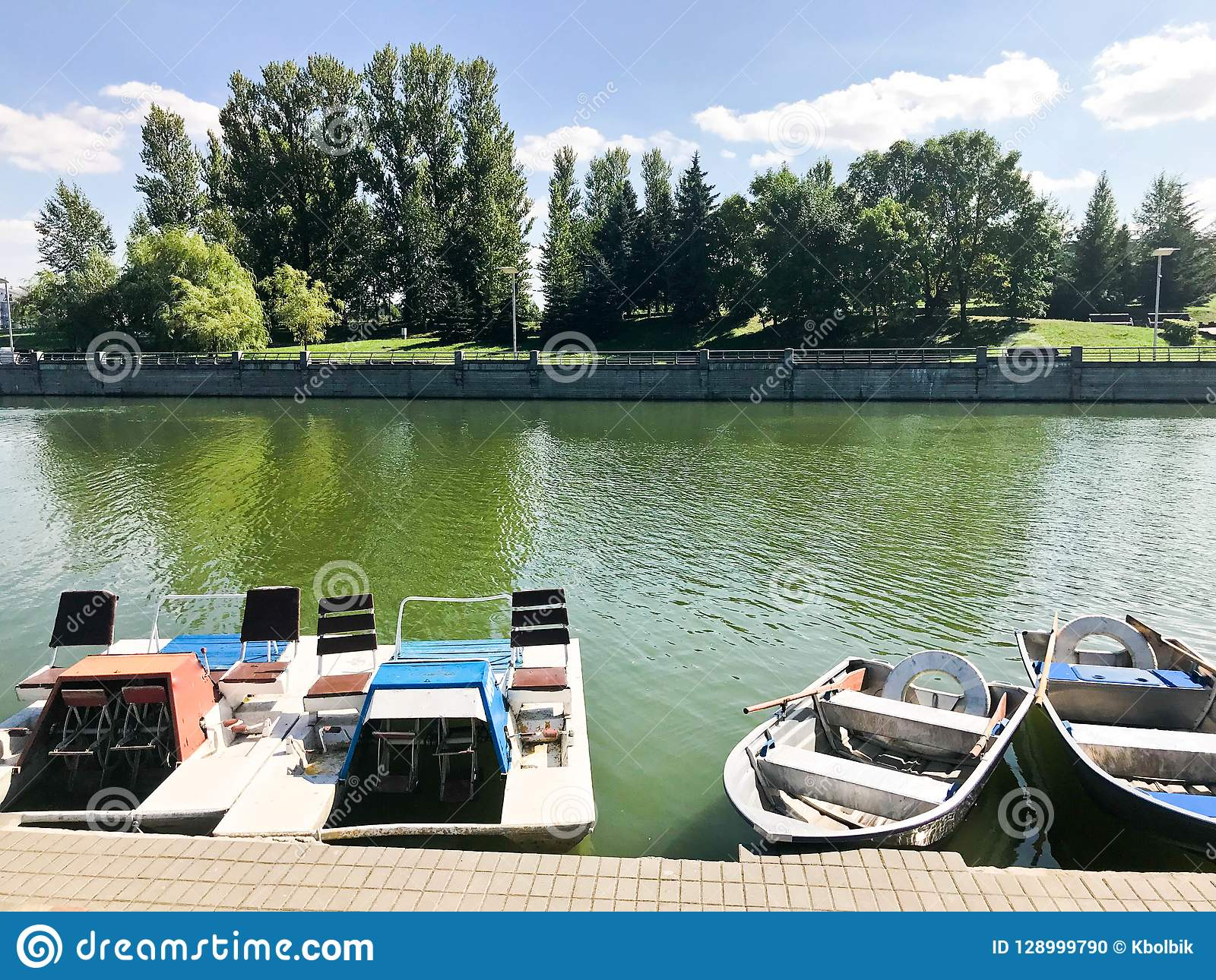 Boats and catamarans on a pond lake in a river canal with green flowered water are moored on the shore