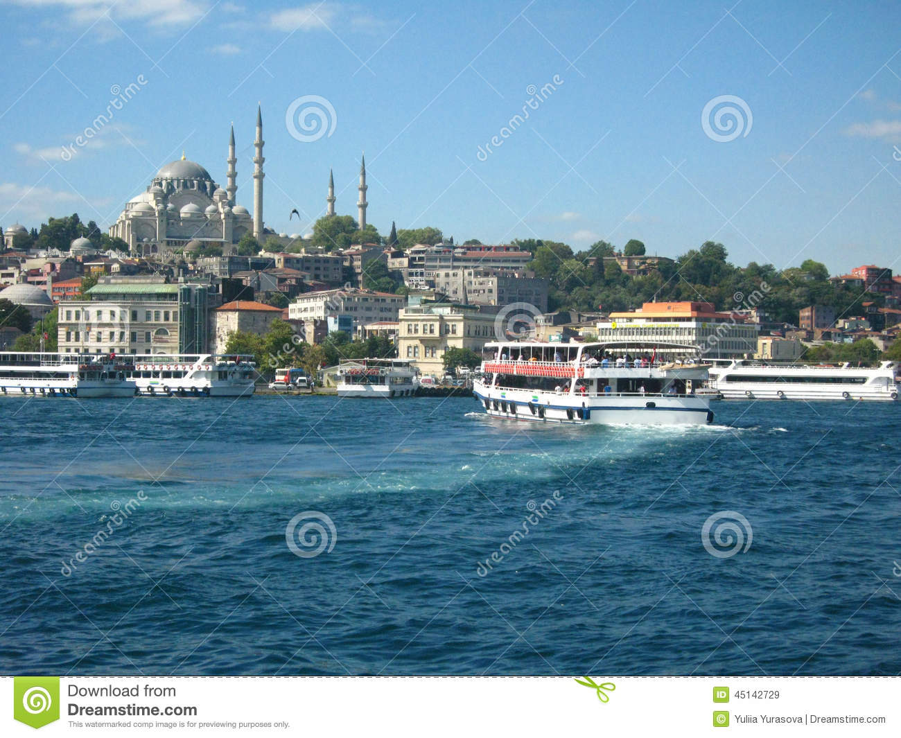 Boats crossiog Bosphorus in the city of Istanbul, Turkey and a mosque with high minarets on the background
