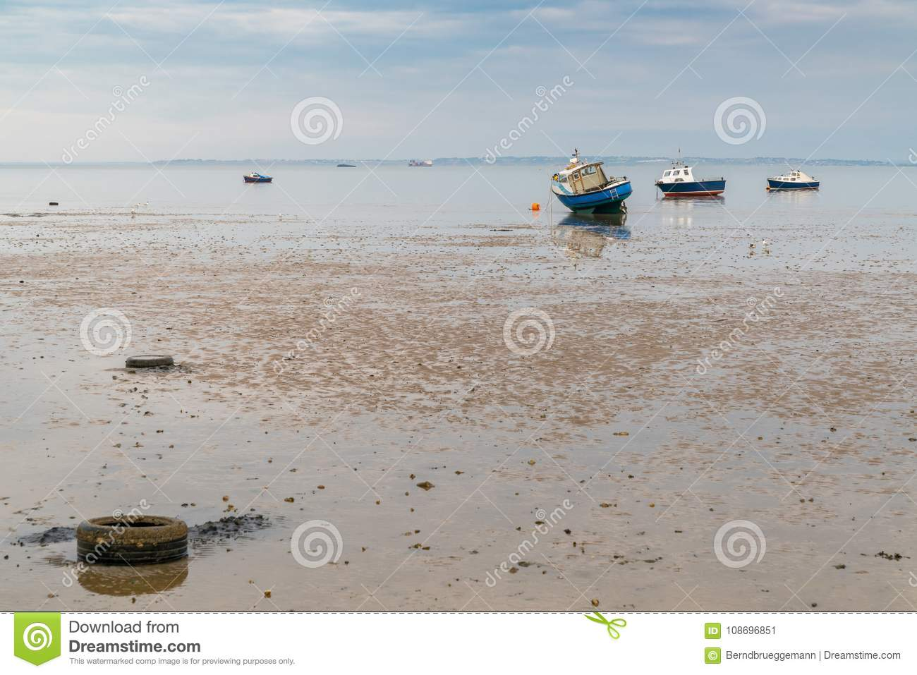 Boats at low tide on the shore of the River Thames