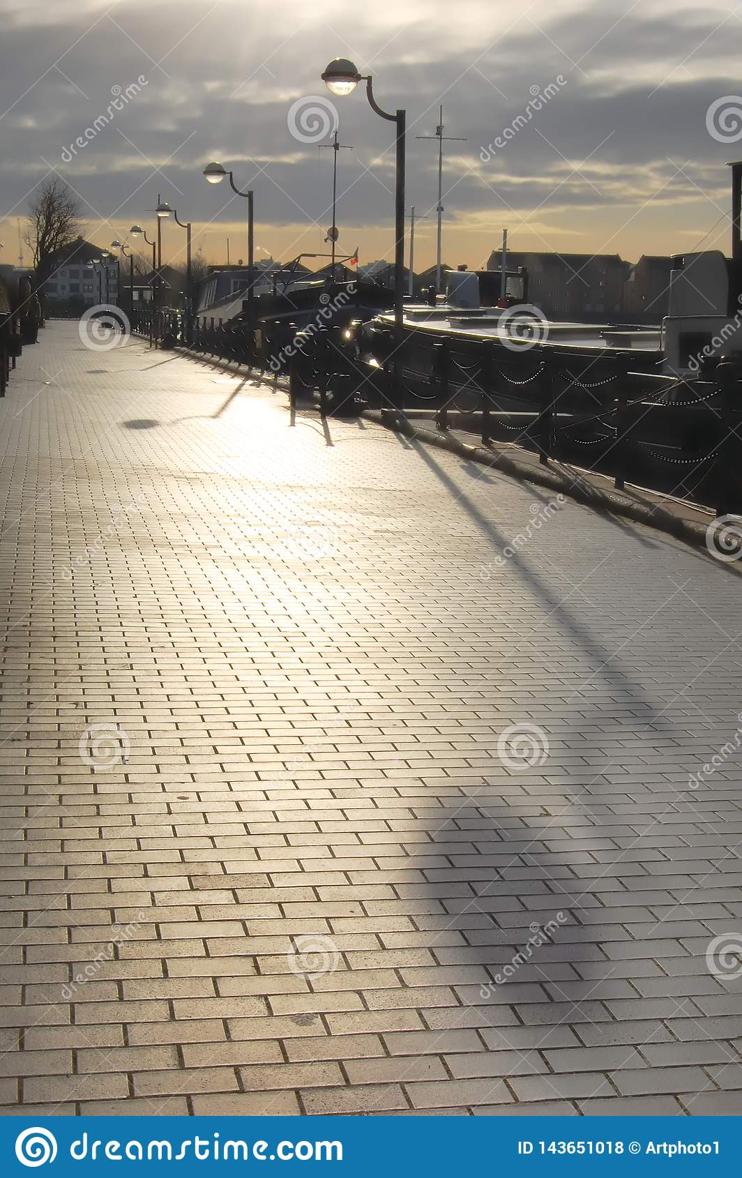 Boats moored next to footpath with long lamp post shadows