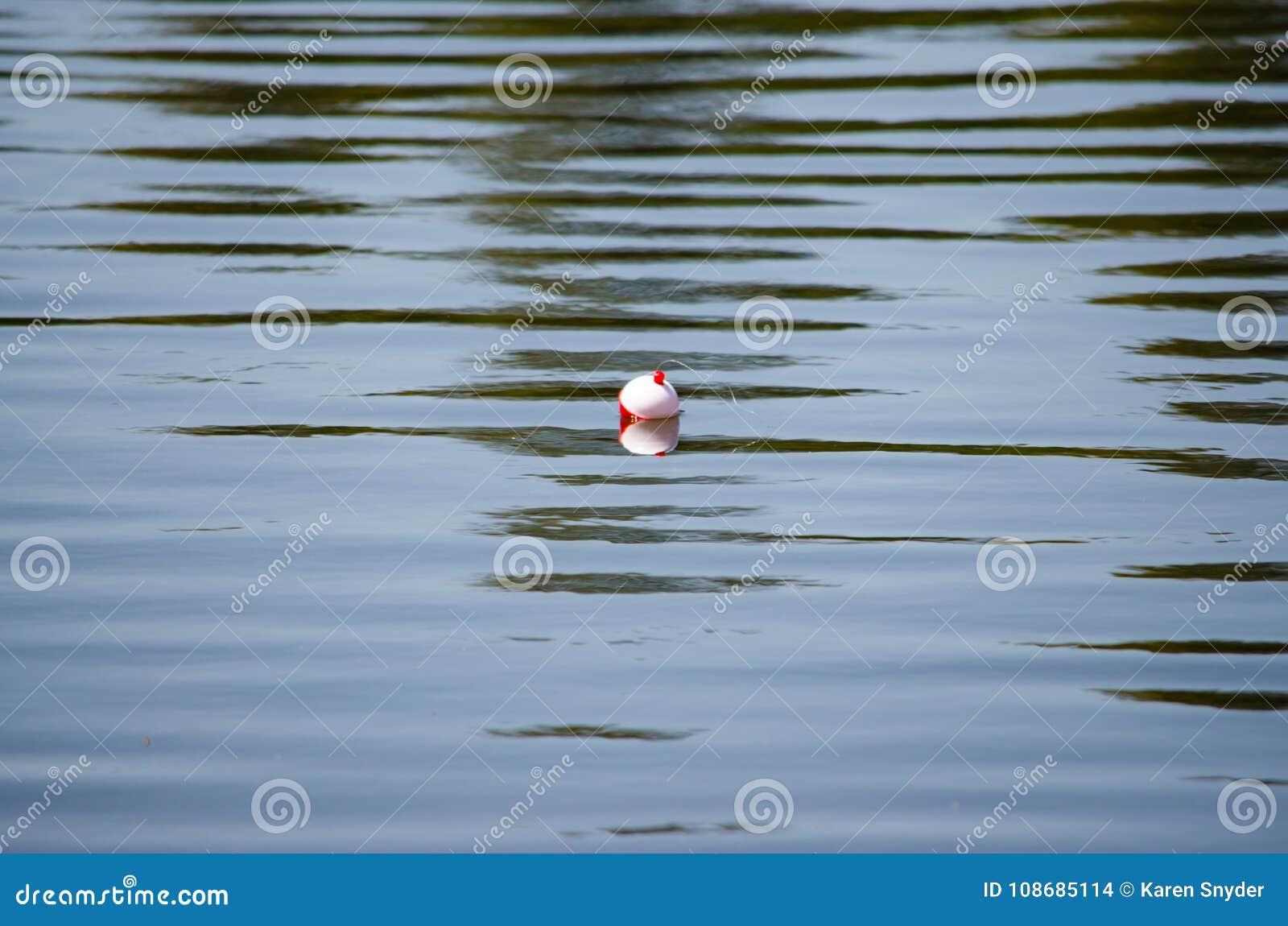 Bobber da pesca que flutua na água