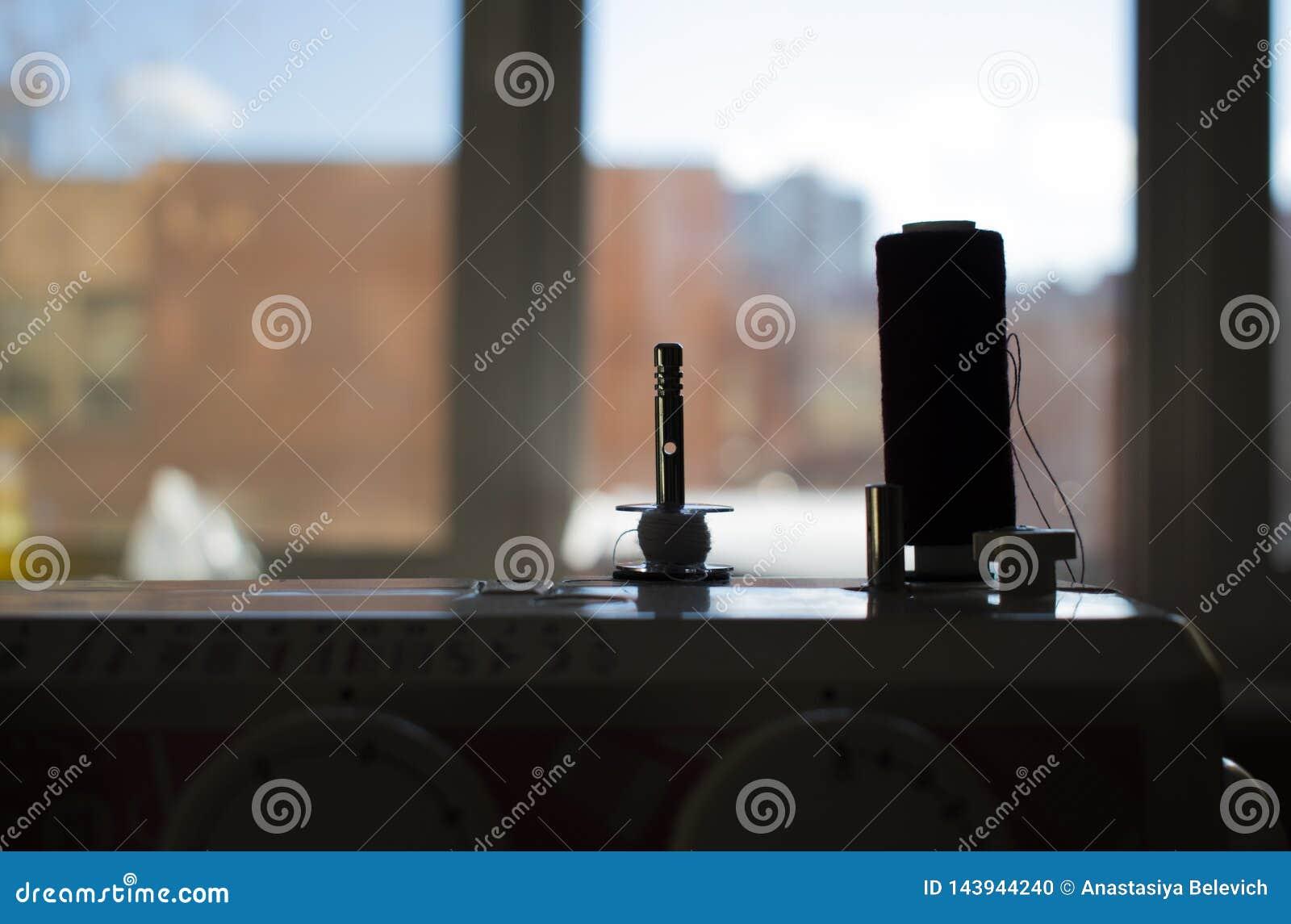 Bobina del filo sulla siluetta del primo piano della macchina per cucire