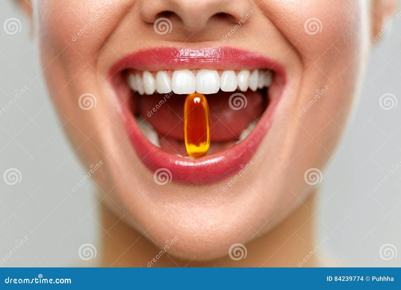 Boca bonita da mulher com o comprimido nos dentes Menina que toma vitaminas