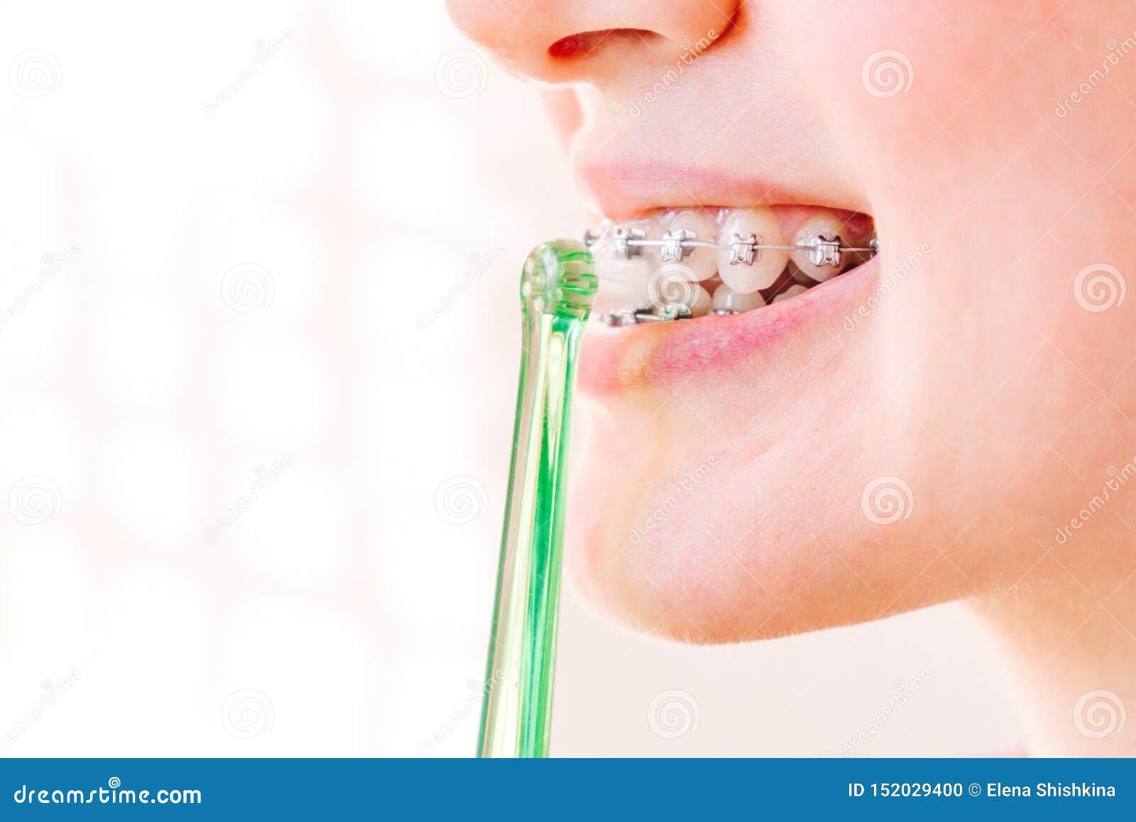 Boca femenina con el primer de los apoyos con el cepillo de dientes en perfil
