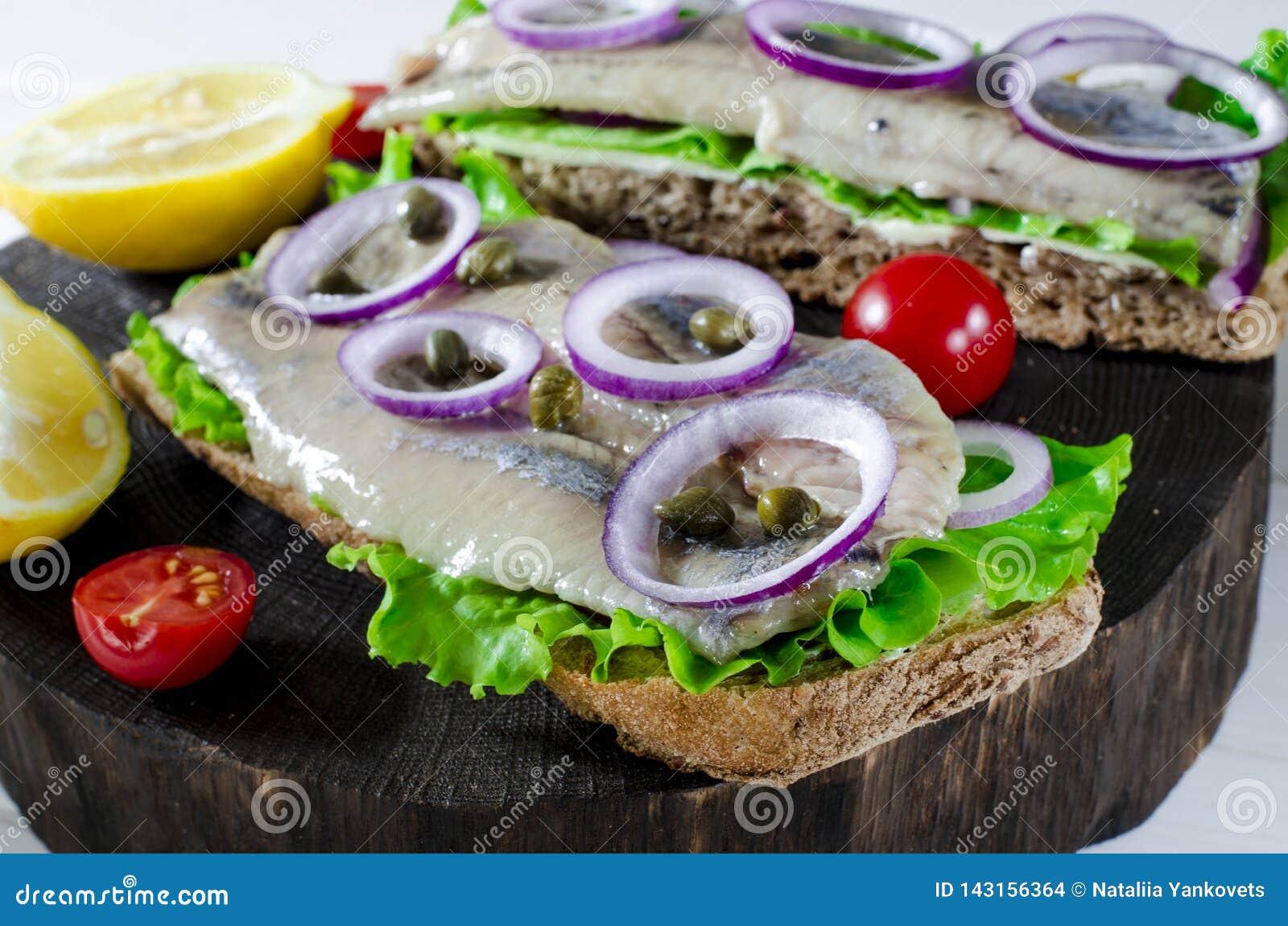 Bocadillo con los arenques salados, la mantequilla y la cebolla roja en vieja tabla de cortar rústica Foco selectivo