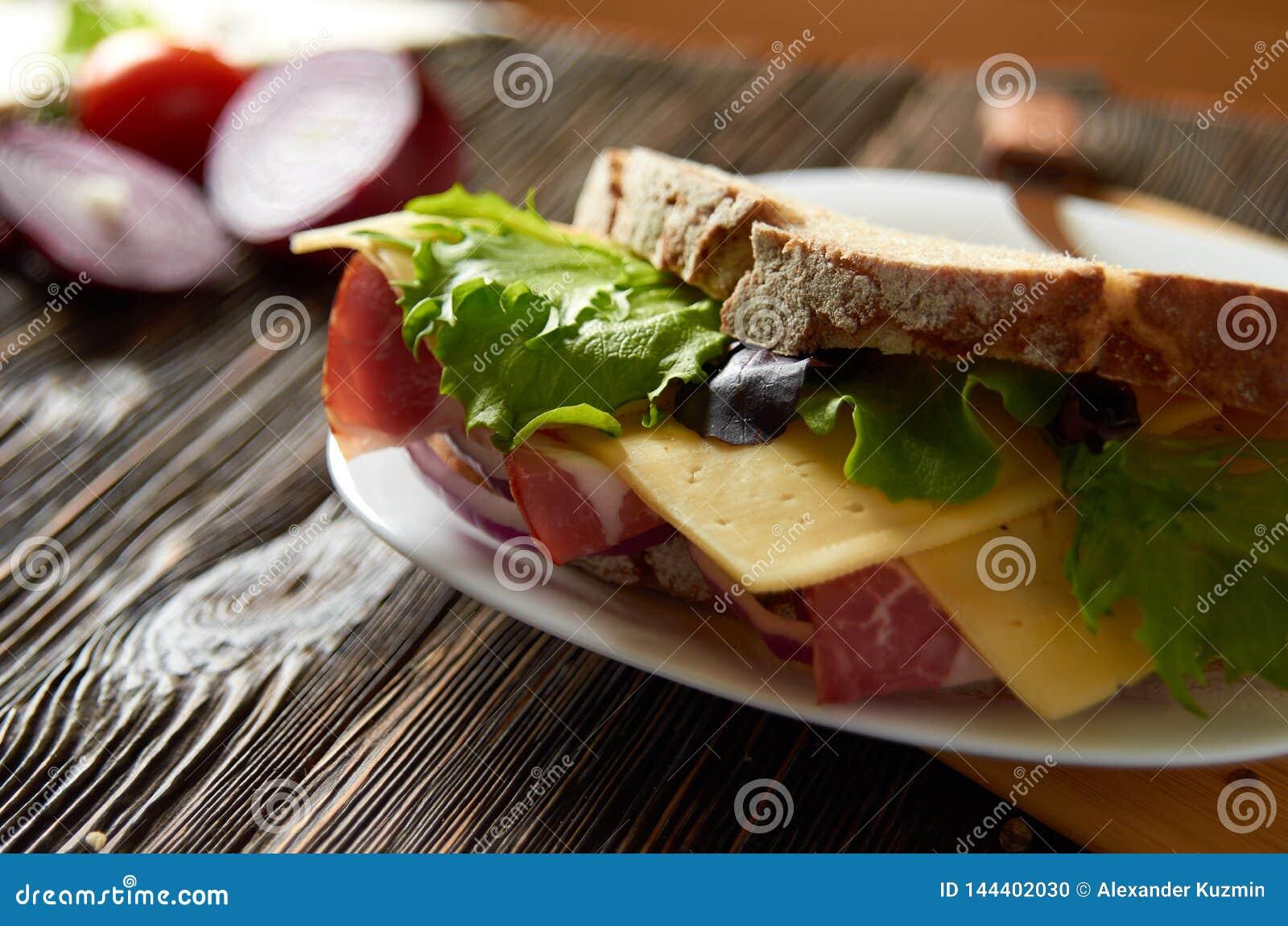 Bocadillo con tocino, queso e hierbas en una placa