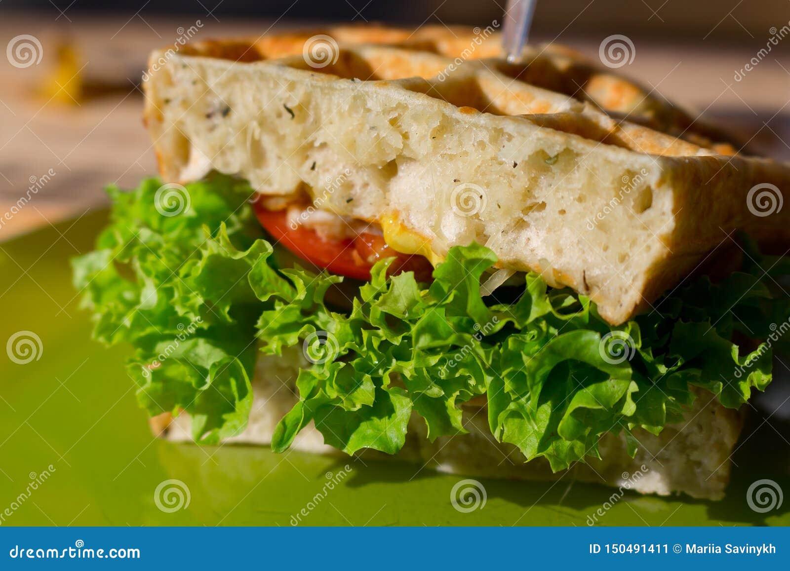 Bocadillo de club sabroso con el pan blanco de la galleta, tomate, cebolla, ensalada en la placa verde al aire libre