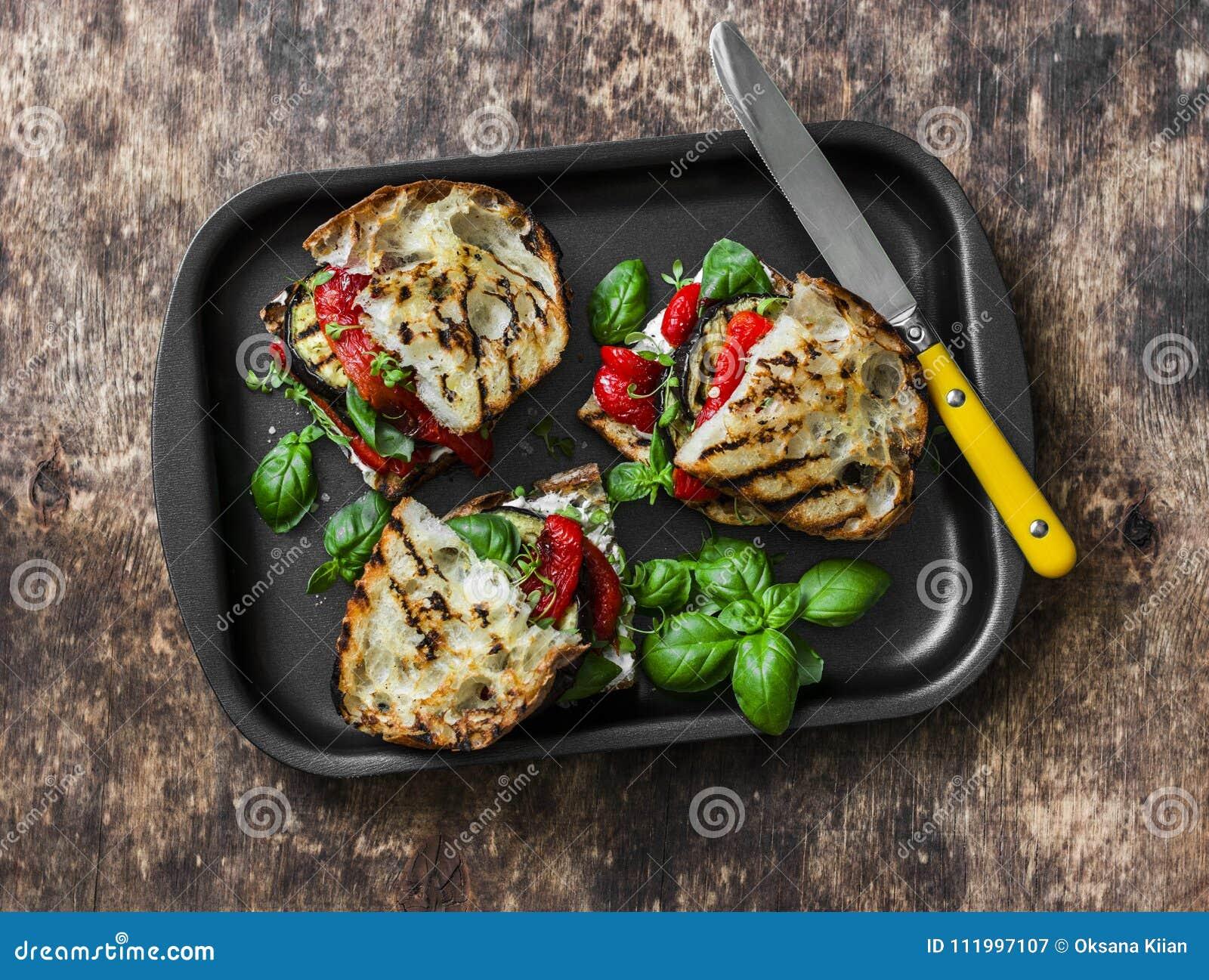 Bocadillos asados a la parrilla comida campestre de las verduras del verano Berenjena, paprikas, ciabatta, salsa del yogur, bocad