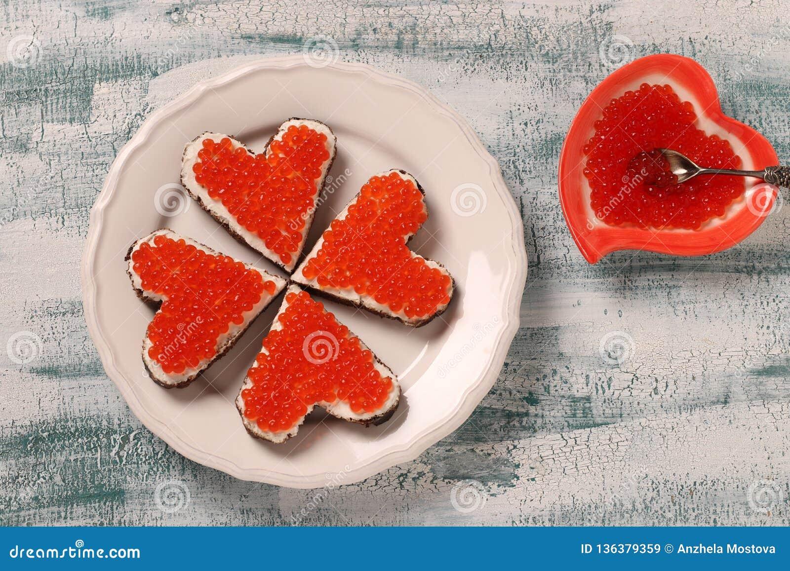 Bocadillos con el caviar y el queso cremoso rojos en la forma de un corazón para el día de tarjeta del día de San Valentín