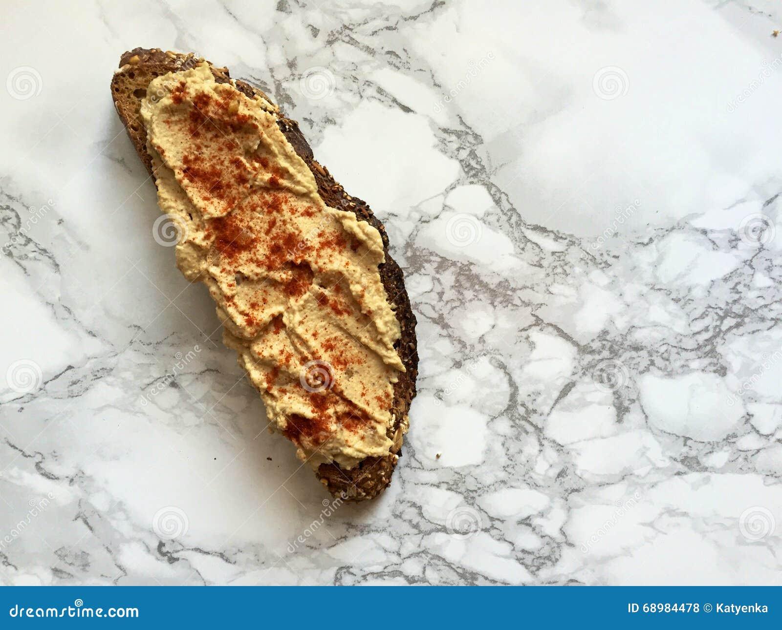 Bocado del vegano: Tostada entera artesanal del grano con hummus y paprika