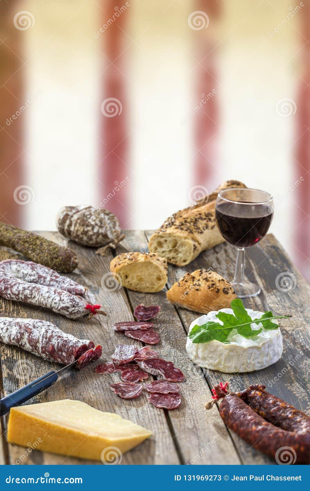 Bocados franceses con el vino - diversos tipos de quesos, pan, suassages secos, charcuterie, vid roja en un fondo gris