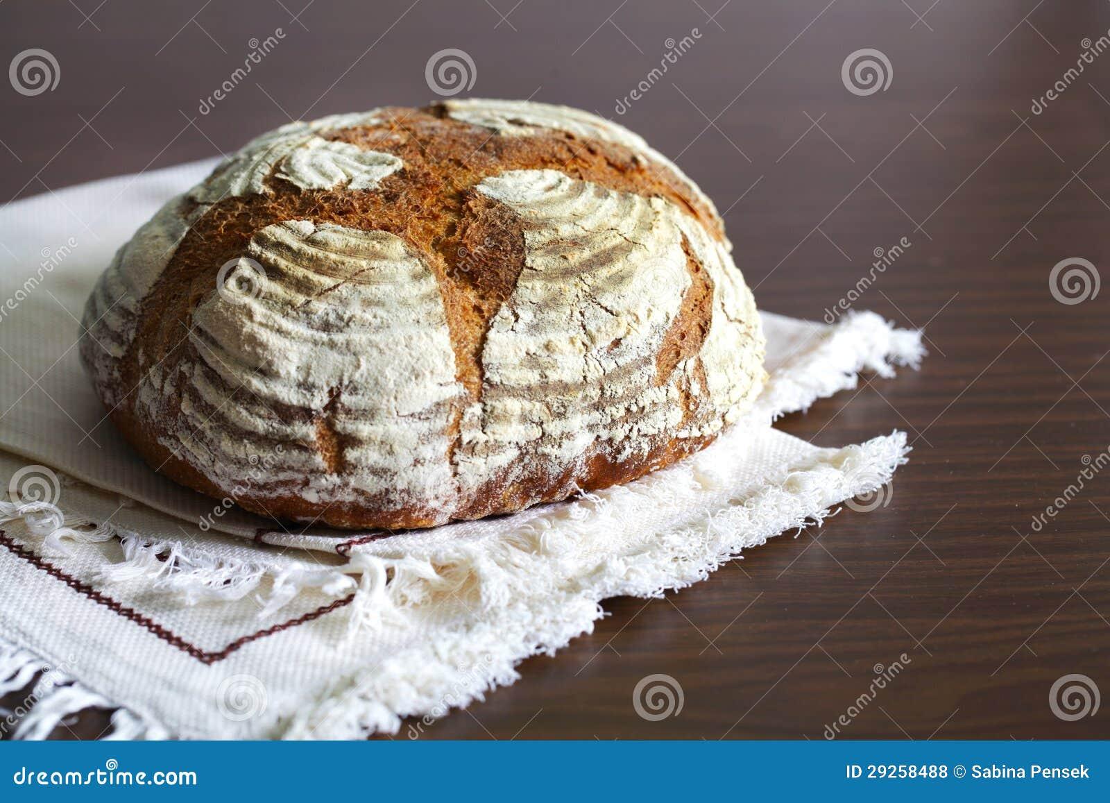 Bochenek rzemieślnika żyta chleb, odkurzający z mąką, na stołowym płótnie