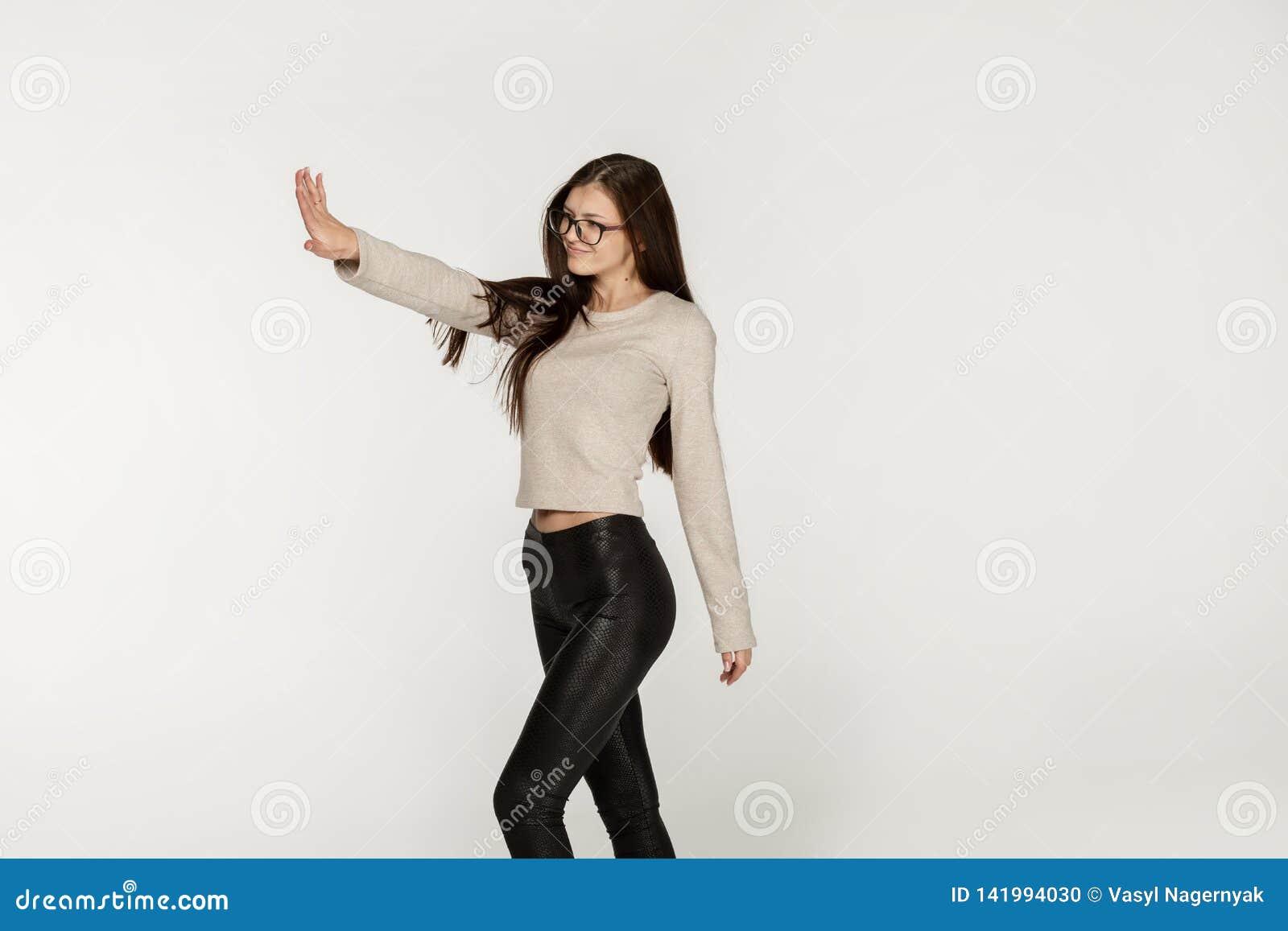 Bocznego widoku fotografia radosna szczęśliwa europejska dziewczyna jest ubranym czarnych szkła i leggings z długim brunetka włos