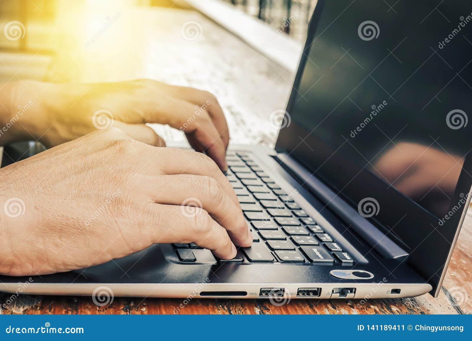 Bocznego widoku strzał pracować przy kawiarnią z laptopu mężczyzną pisze blogu samiec ręki na klawiaturze