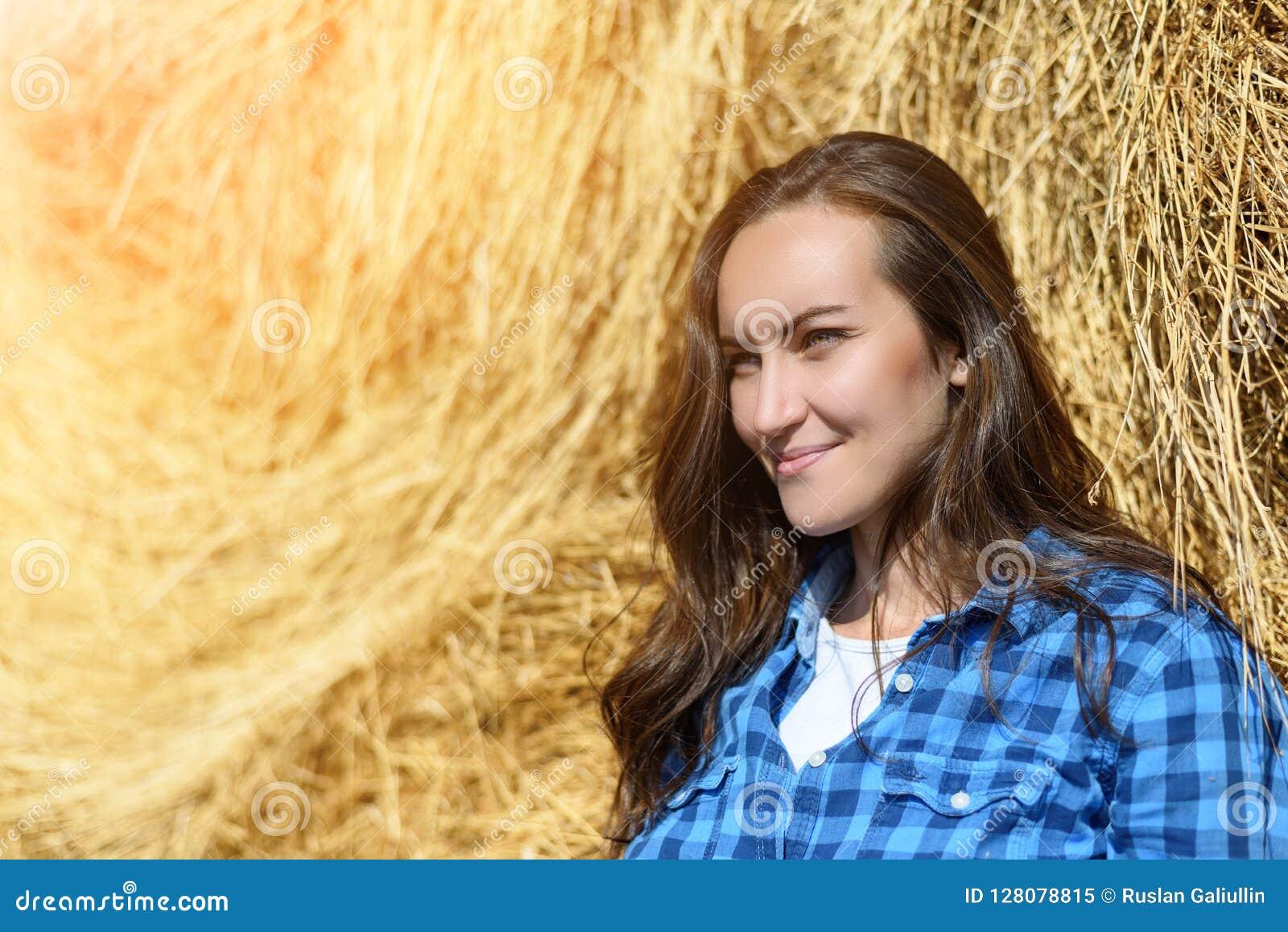 Boczny portret uśmiechnięta młoda kobieta stoi opierać na haystack w błękitnej klatkowej mężczyzna ` s koszula