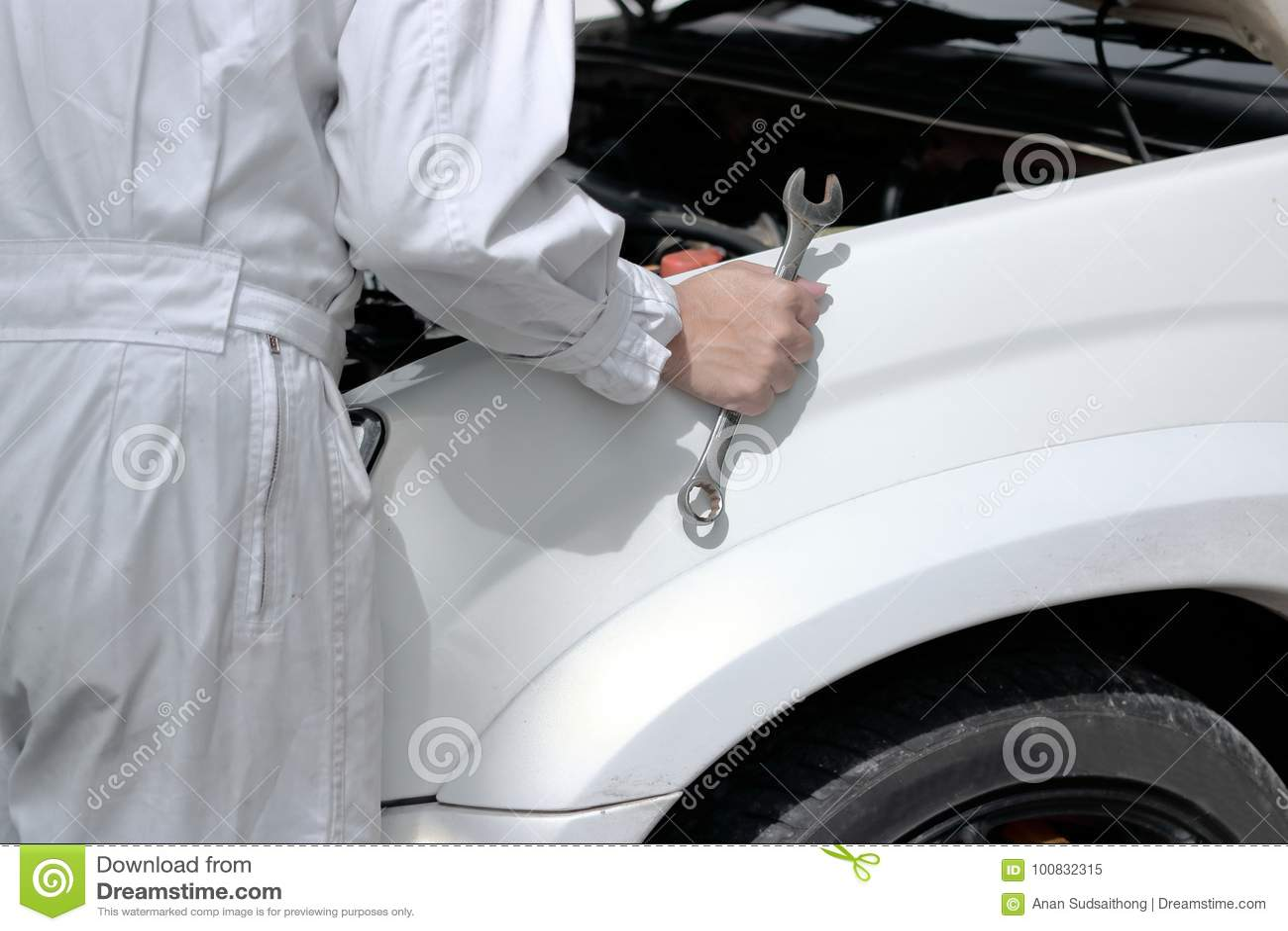 Boczny widok automobilowy mechanik diagnozuje silnika pod kapiszonem samochód przy remontowym garażem w mundurze z wyrwaniem
