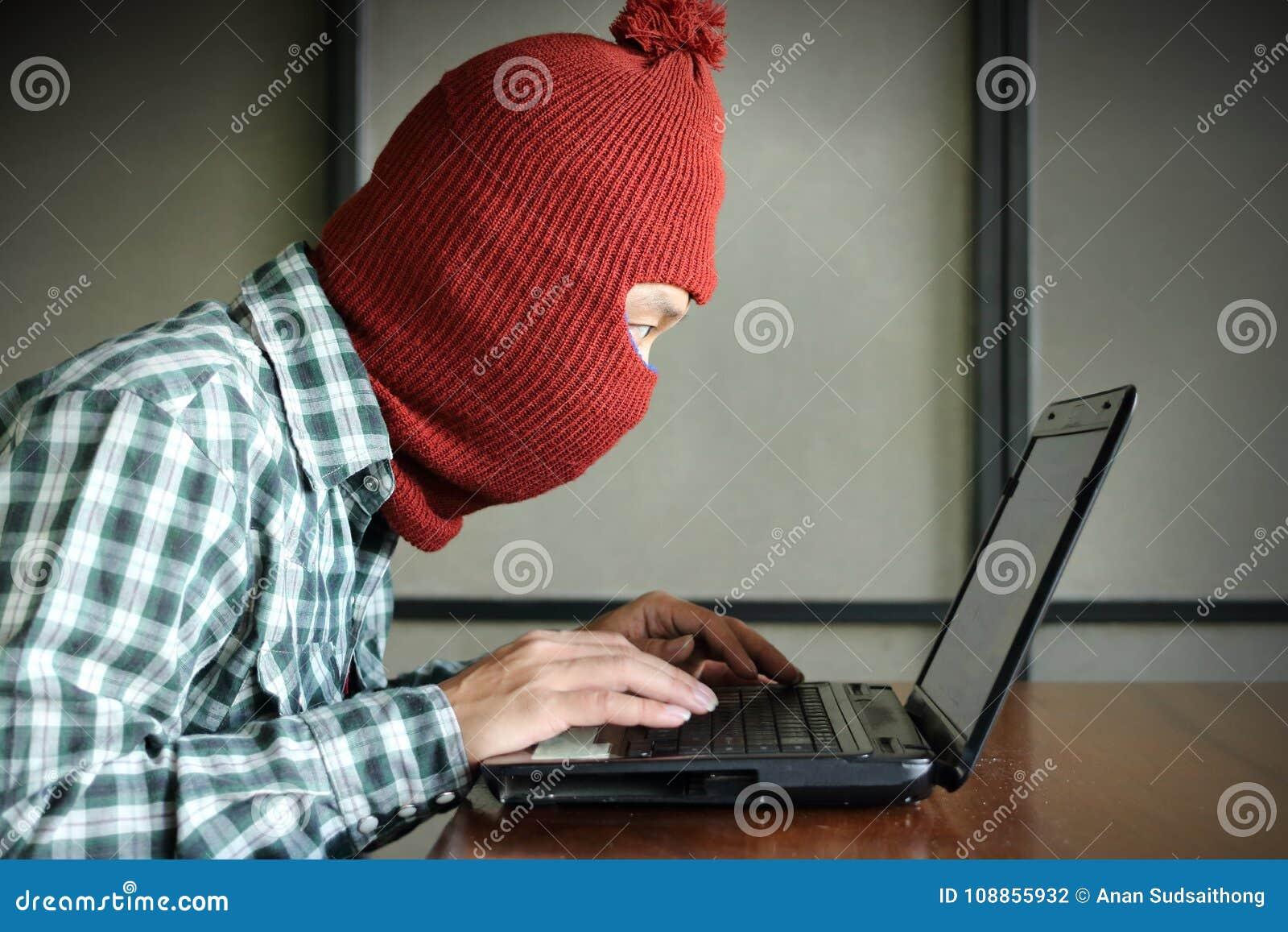 Boczny widok jest ubranym balaclava patrzeje laptop i kraść ważna informacja dane zamaskowany hacker Sieci priv i ochrona