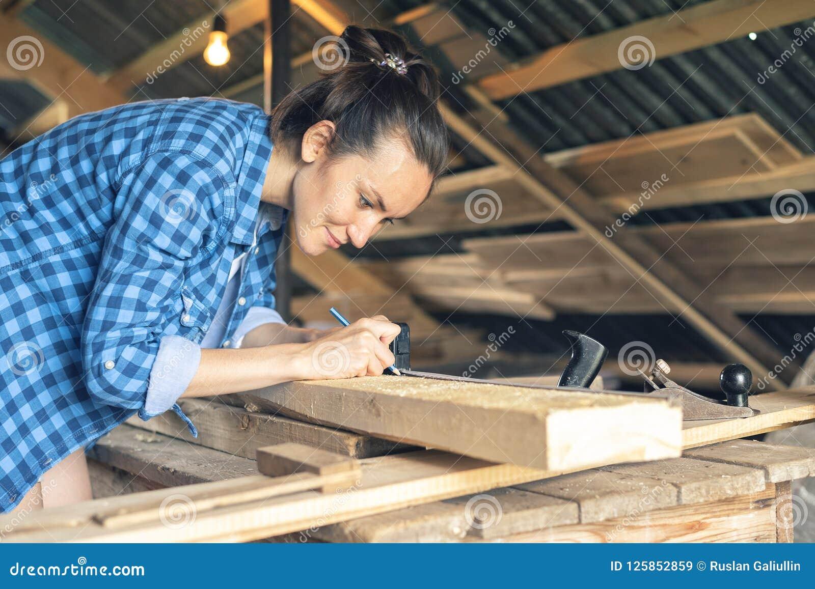Boczny widok kobieta cieśla rysuje na drewnianej deski cięcia linii