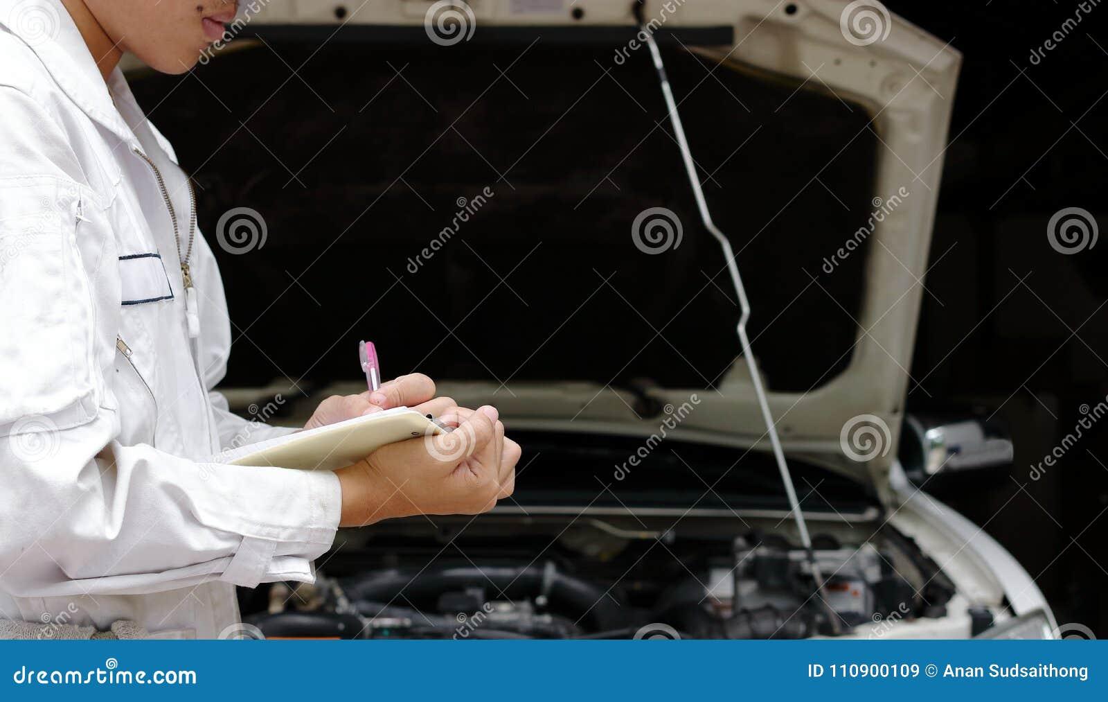 Boczny widok młody fachowy mechanik w jednolitym writing na schowku przeciw samochodowi w otwartym kapiszonie przy remontowym gar