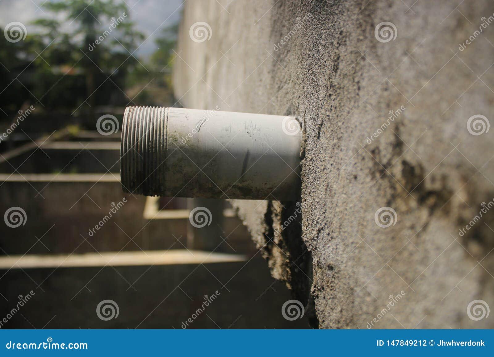 Boczny widok niedokończonego drenażu fajczany wtykać za popielatej ścianie