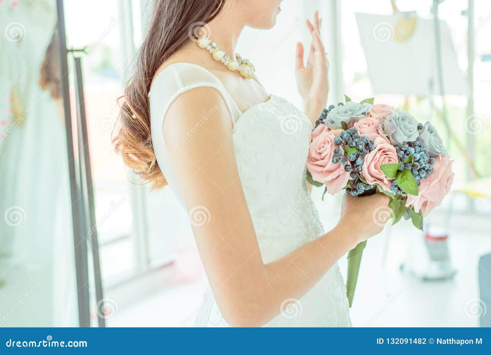 Boczny widok panna młoda trzyma ślubnego bukiet i pokazuje ona ślub
