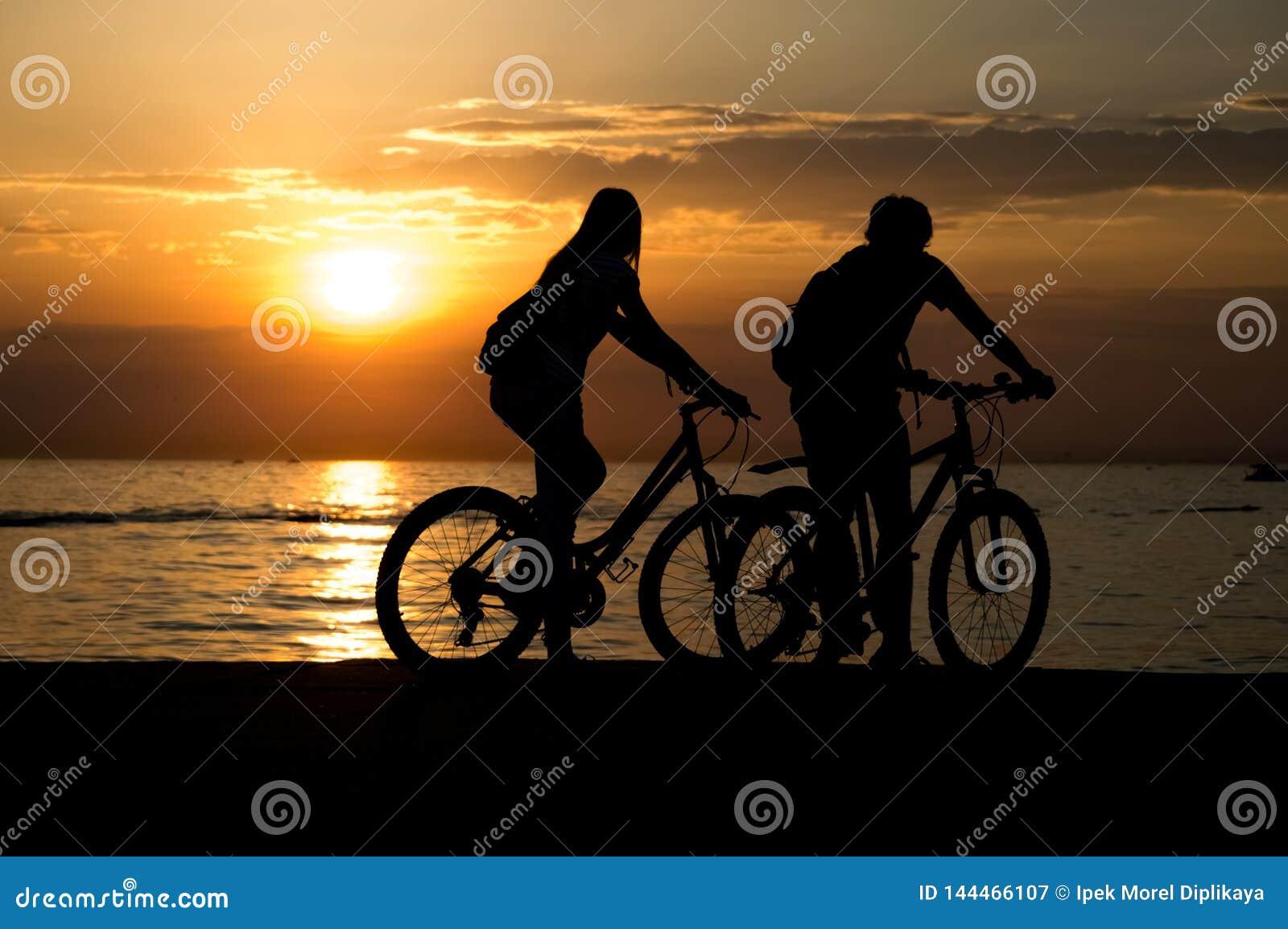 Boczny widok pary pozycja na seashore z ich cieszyć się zmierzchem i bicyklami