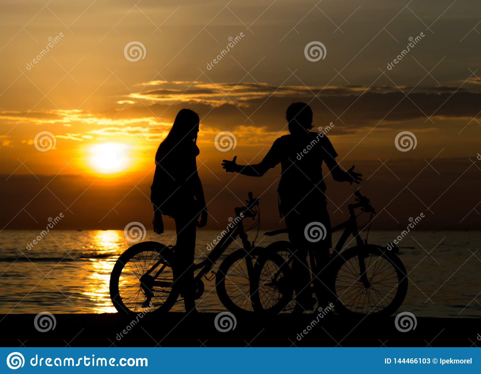 Boczny widok pary pozycja na seashore z ich cieszy? si? zmierzchem i bicyklami